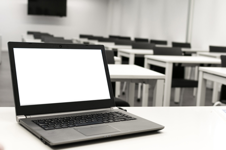 Foto de Laptop, online business, teacher work in the classroom.Laptop put on a table or desk located in empty room. - Imagen libre de derechos