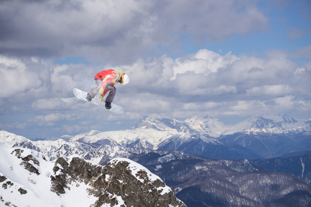 Snowboard rider jumping on snowy mountains. Extreme snowboard freeride sport.