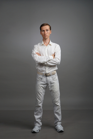 Serious young man with crossed hands standing against grey background.