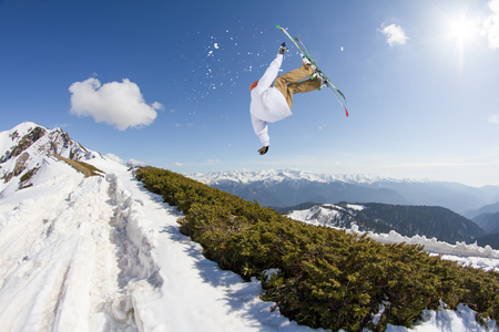 Jumping skier in winter snowy mountains. Extreme sport, freeride.