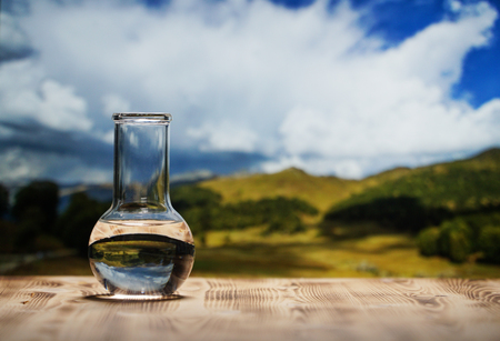 Photo pour Clean water in a glass laboratory flask on wooden table on mountain background. Ecological concept, the test of purity and quality of water. - image libre de droit