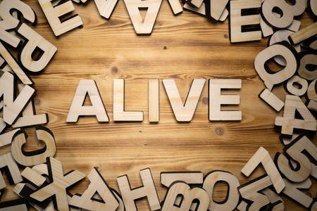 Foto de ALIVE word made with block letters lying on wooden board - Imagen libre de derechos