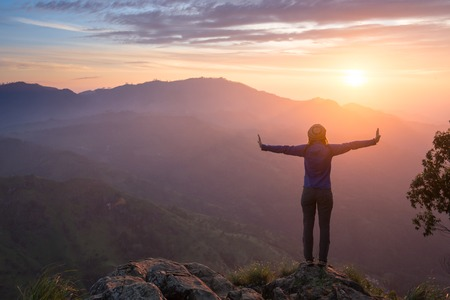 Foto de Happy celebrating winning success woman at sunset or sunrise standing elated with arms raised up above her head in celebration of having reached mountain top summit goal during hiking travel trek. - Imagen libre de derechos