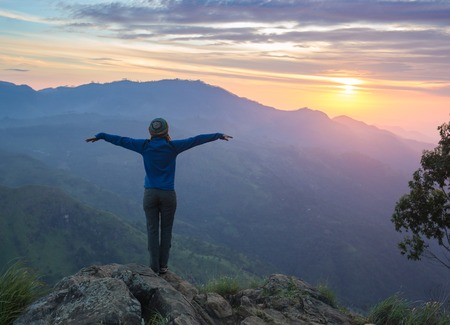 Photo for Happy celebrating winning success woman at sunset or sunrise standing elated with arms raised up above her head in celebration of having reached mountain top summit goal during hiking travel trek. - Royalty Free Image