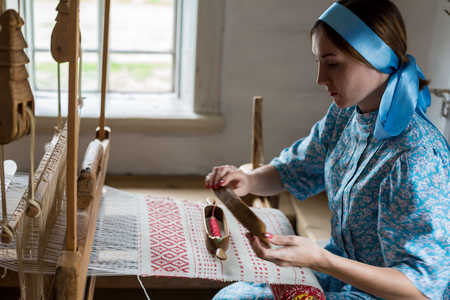 The woman is weaving the colorful cotton robe or dress by using wooden loom in the local village in Russia