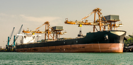 Photo for A Bulk Cargo ship/vessel berthed at the Harbor, being offloaded by grabs of cranes. Visible are vessel's draft marking which depicts that it is nearly emptied and contains no ballast. Import & Export - Royalty Free Image