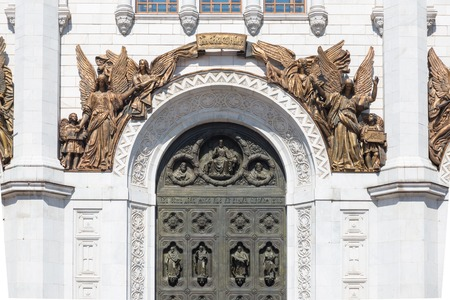 Arch above the large middle gate of the Cathedral of Christ the Savior in Moscow, Russia. The high relief with  four angels with outspread wings, holding the charter that says - God's Power with us and two angels. The image of the blessing Christ the S