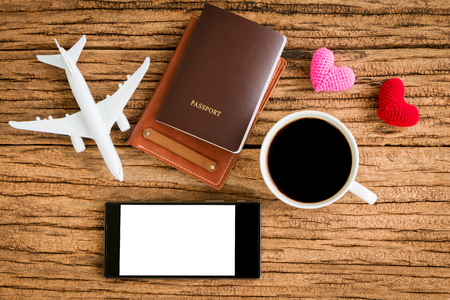 Photo for Passport and black coffee and a wallet and a plane model and red heart and smartphone with copy space for ad text put on the wood texture for travel planning and advertising business concept. - Royalty Free Image