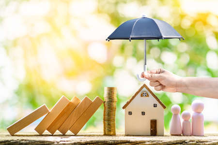 Photo pour Collect gold coin and woman hand hold open the black umbrella for protect the home and family from hazard falling wood block in the public park, Saving money for buy insurance of real estate concept. - image libre de droit