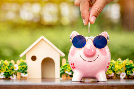 Foto de Businessman hand hold a coin is save to the piggy bank with growing a interest and wooden home model for family in the public park, Business investment and loan for real estate in the future concept. - Imagen libre de derechos