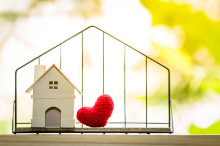 Photo pour A house model and red heart put in the shelf with shape home for family love concept, on the wooden floor in public park. - image libre de droit