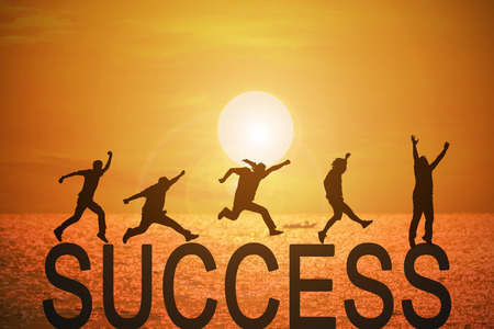 Silhouette group of young mans jumping over the success words with beautiful sunset at the sea background, concept for success and victory in business.