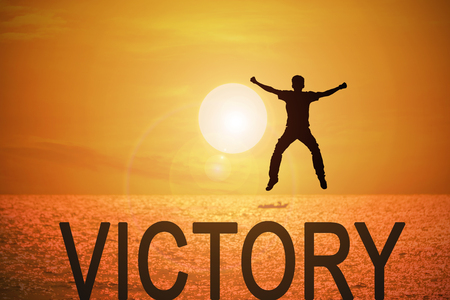 Silhouette of young man jumping over the victory words with beautiful sunset at the sea background, concept for success and victory in business.