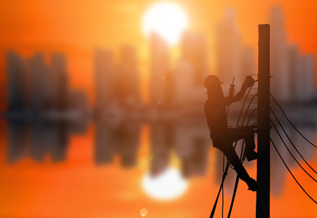 Photo pour Silhouette of an electrician are climbing on electric poles to install power lines with the beautiful sunset at the city background. - image libre de droit