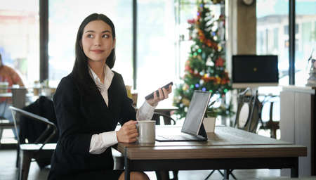 Photo pour Businesswoman in formal suit wearing wireless earphone and working with tablet computer at modern cafe. - image libre de droit
