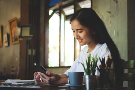 Photo pour Portrait of happy young woman working on tablet pc while sitting at her working place in office. - image libre de droit