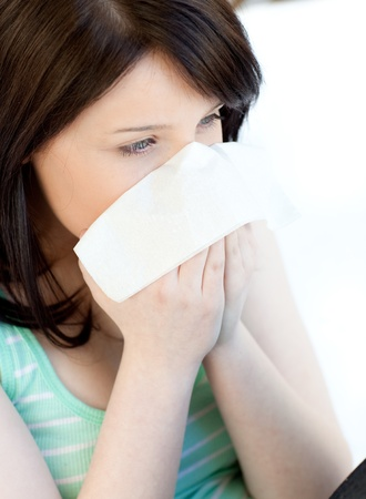 Portrait of a sick brunette teen girl blowing