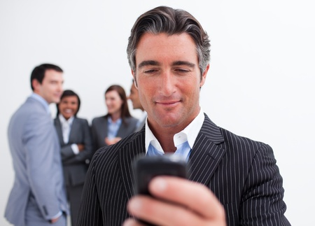 Confident manager sending a text with a mobile phone