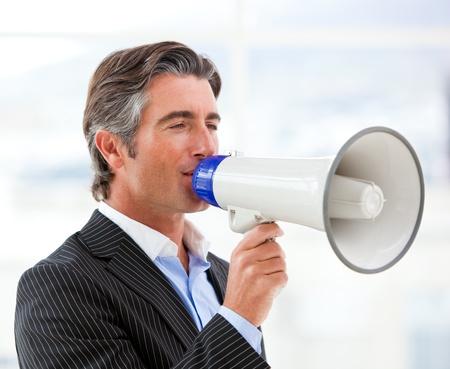 Confident businessman yelling through a megaphone