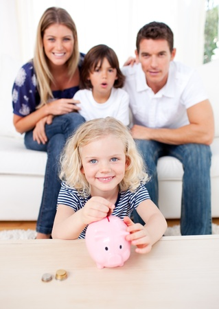 Blond little girl inserting coin in a piggybank