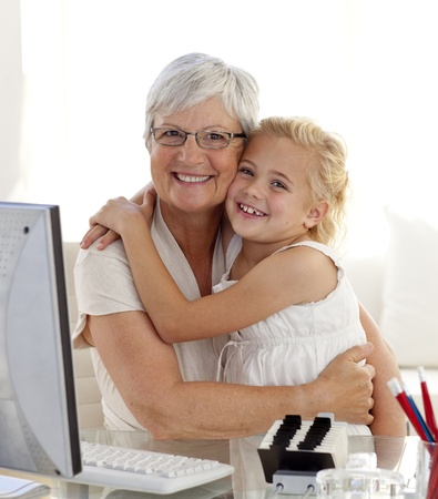 Granddaughter and grandmother hugging and using a computer