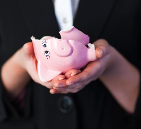 Business woman holding a broken piggy bank