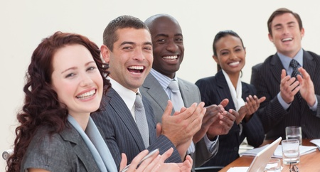Cute multi-ethnic business team applauding a presentation