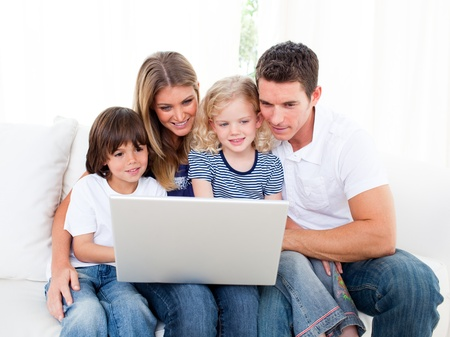 Portrait of a jolly family using a laptop sitting on sofa