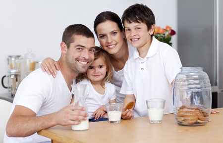 Happy family eating biscuits and drinking milk