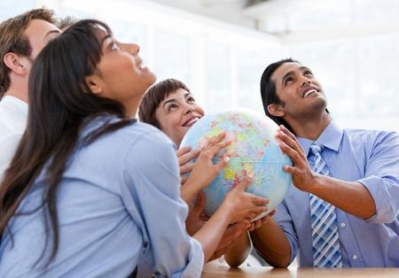 Foto de International business team holding a terrestrial globe - Imagen libre de derechos