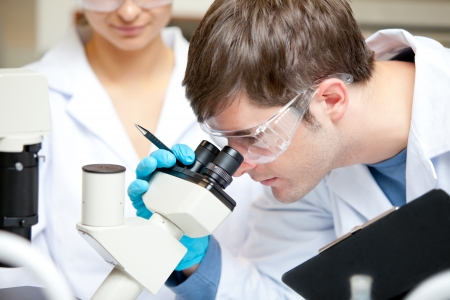 Caucasian male scientist holding pen and clipboard looking through a microscope