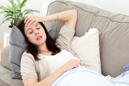 Indisposed woman feeling her temperature while resting on the sofa