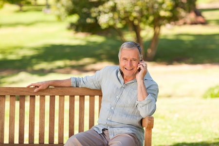 Retired man phoning in the park
