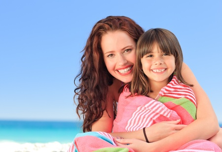 Smiling woman with her daughter in a towel