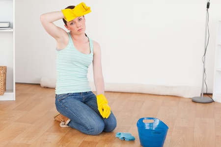 Cute red-haired woman having a break while cleaning the floor at home