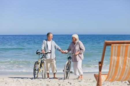 Elderly couple with their bikes on the beach