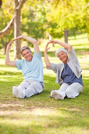 Elderly couple doing their stretches in the parkの写真素材