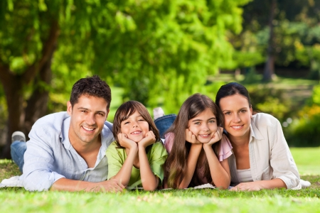 Foto de Family lying down in the park - Imagen libre de derechos