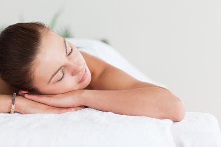 Photo pour Close up of a cute brunette lying on a massage table in a spa - image libre de droit