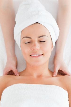 Beautiful brunette enjoying a shoulder massage with her eyes closed