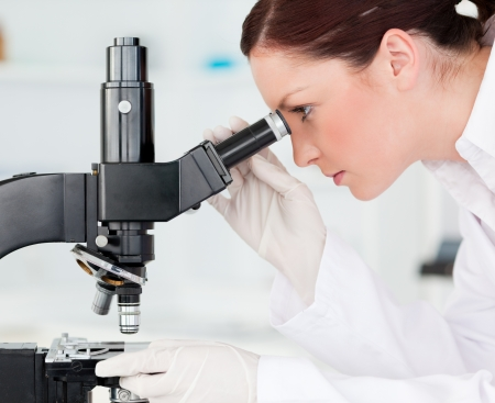 Attractive red-haired scientist looking through a microscope in a lab