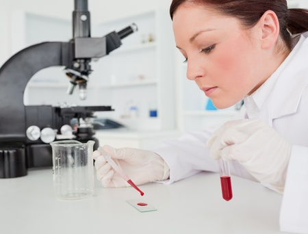 Cute red-haired female scientist doing an experiment in a lab
