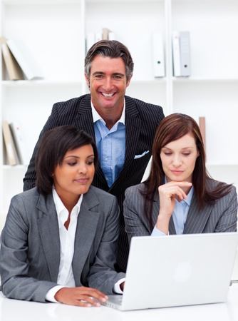 Serious businesswomen and their colleague working at a laptop