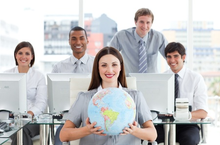 Foto de Pretty businesswoman and her team showing a terrestrial globe - Imagen libre de derechos