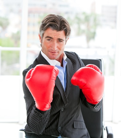 Self-assured businessman wearing boxing gloves