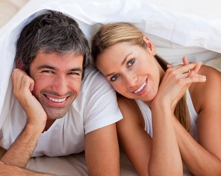 Photo pour Loving couple having fun lying on bed - image libre de droit