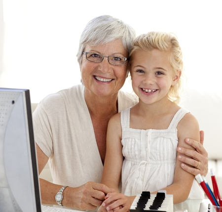 Portrait of granddaughter and grandmother using a computer