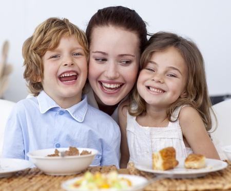 Children having breakfast with their mother
