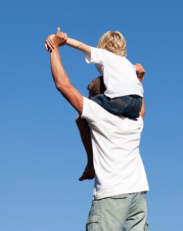 Son sitting on his father's shoulders の写真素材