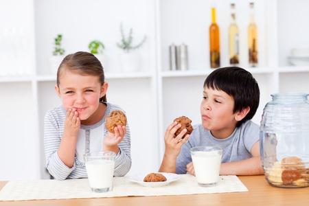 Happy Siblings eating cookies and drinking milk